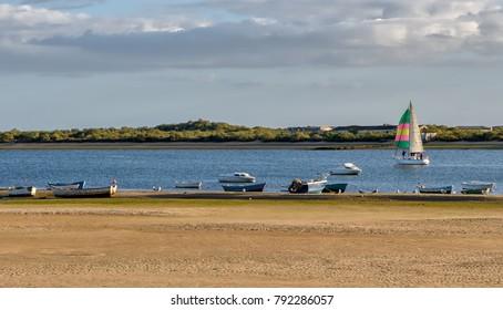 Colorful sailboat and fishing boats at Piedras river mouth at El Rompido, Huelva