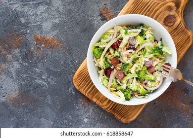 Colorful salad made with broccoli, grapes, cabbage, red onion, carrots, top view, copy space for text, selective focus