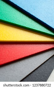 Colorful samples of foamed polyvinyl plates used in the graphic industry.