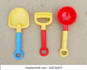 colorful sand castle toys - spoon, fork and spade on beach
