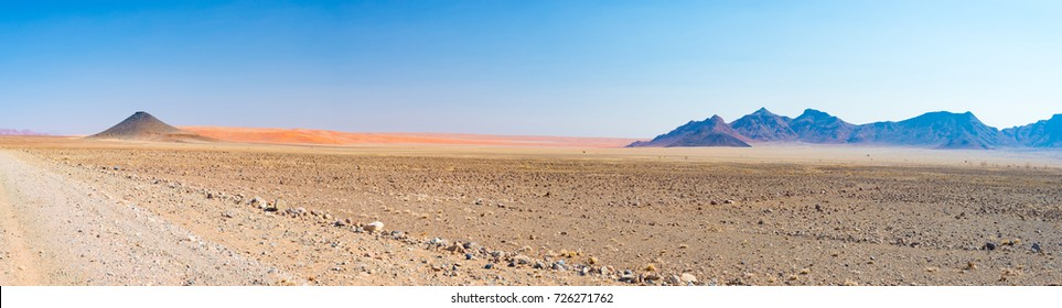 Colorful sand dunes and scenic landscape in the Namib desert, Namib Naukluft National Park, tourist destination in Namibia. Travel adventures in Africa. High resolution panorama.
