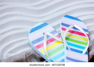 colorful sandals and fishnet lying on the sand