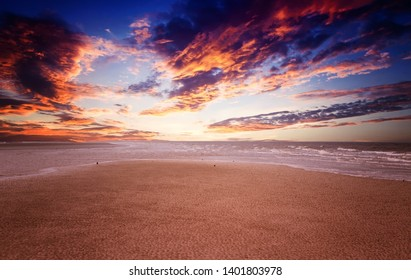 colorful sandy beach at sunset with clouds