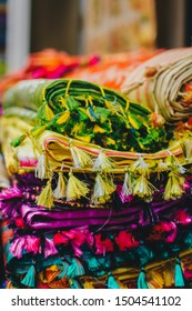 Colorful sarees with handmade knotted tassels in a textile store. Shallow depth of field. Copy space for your design.