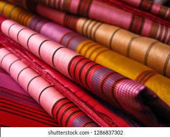 Colorful sarees stacked on each other with patterns visible, pink red yellow colors. Sarees, traditional Indian clothing, prepared in cottage industry of India on traditional handlooms