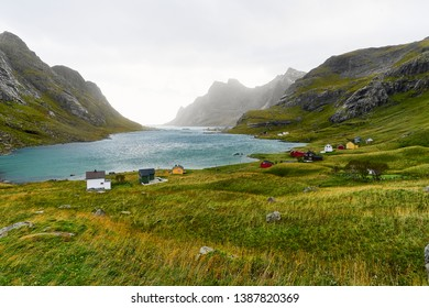 Colorful scandinavian houses at a beautiful bay surrounded by mountains and a small village near Bunes Beach and Vinstad on Lofoten Islands in Norway