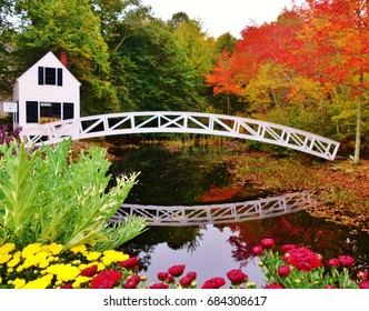 Colorful scene of flowers & autumn trees at the Selectmen's Building in Somesville, Maine on Mount Desert Island. A white walking bridge that crosses a mill stream is reflected in the stream's water.