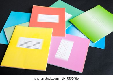colorful school notebooks on black background