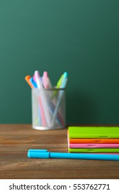 Colorful school stationery on table on blackboard background