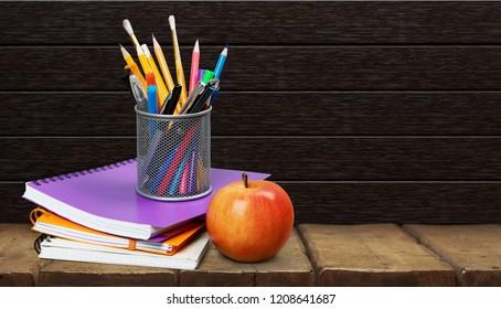 Colorful school supplies on blackboard background