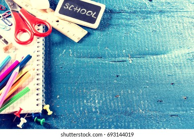 Colorful school supplies over blue background with copyspace. Back to school concept