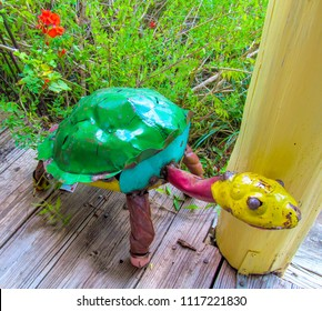 Colorful Sculpture of Turtle on wooden floor near green grass.  Recycled Scrap Metal Yard Art. Beautiful garden decor object. Summer view  outdoors.
