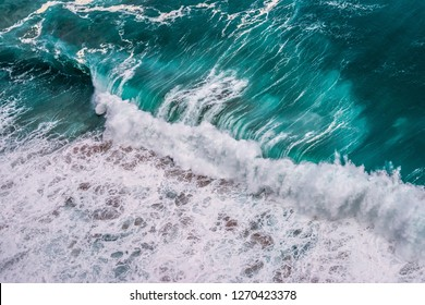 Colorful sea background. Turquoise ocean water with waves, spray and white foam.