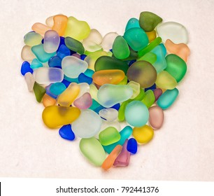 Colorful Sea Glass in the shape of a Heart on a white background