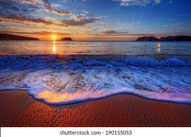 Colorful seaside beach sunrise with bright distant reflections 2