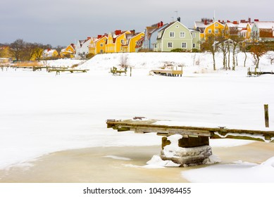 Colorful seaside homes on Salto island in Karlskrona, Sweden. Ice and snow in the wintry landscape.