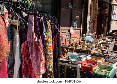 Colorful secondhand vintage clothes,  judaica objects and other Israeli souvenirs at the flea market in Jaffa (Israel). Selective focus on the dresses.