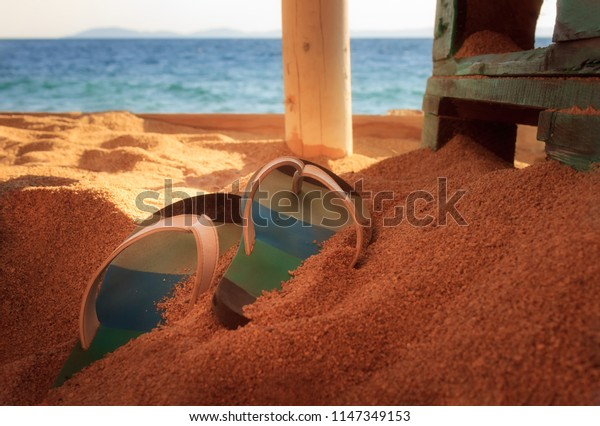 Colorful, selective focus flip-flops on a golden sand on a beach in a bar with wooden furniture and soft focus sea