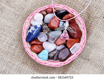Colorful semi-precious stones in basket and a crystal decorative figure of angel.