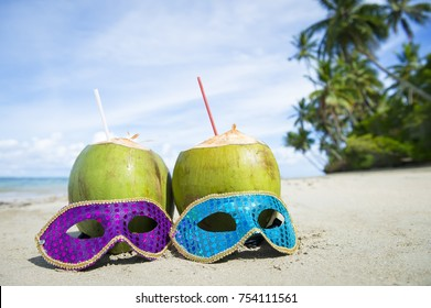 Colorful sequined carnival masks and fresh green coconut drinks on a palm fringed beach in Brazil.