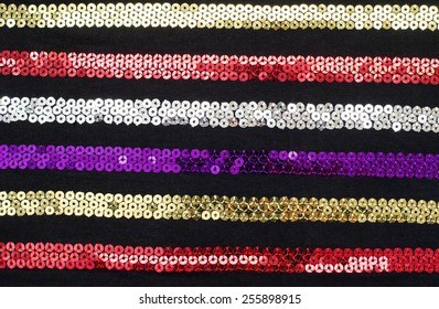 Colorful sequins striped background. Sparkly red, gold, silver, purple stripes pattern on black fabric.