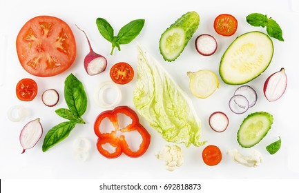 Colorful set of vegetables of red and green color isolated on white background top view, design for vegetable menu. Tomato onion cucumber sweet pepper zucchini Peking cabbage cauliflower radish basil.