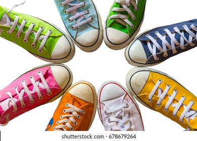 Colorful shoes on white background. Cool youth colorful white yellow green blue black orange gym shoes standing in circle on white background. with copy place top view.