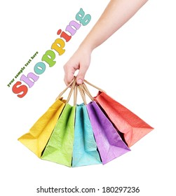 Colorful shopping bags in female hand, isolated on white