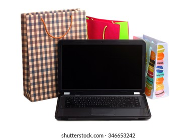 colorful shopping bags for shopping and an open laptop on a white isolated background