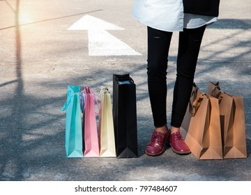 The colorful Shopping bags put on cement ground floor beside lady in black jeans and wear leather shoes,she is  crazy shopaholic person at shopping mall.vintage warm light tone.