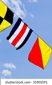 Colorful signal flags flying against blue sky