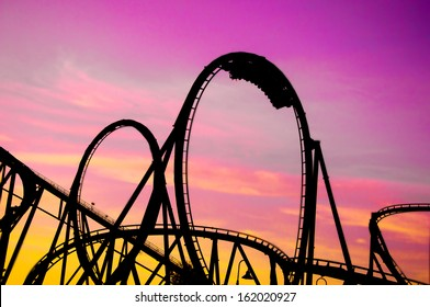colorful silhouette of a roller coaster at sunset, after a sunny day at entertainment park