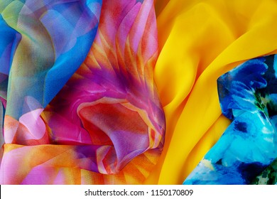 Colorful silk fabric for summer clothes. Sew clothes made of lightweight silk fabric. View from above. The fabric is mixed.