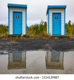 Colorful simple basic outhouses mirrored in big water puddle left from heavy rain