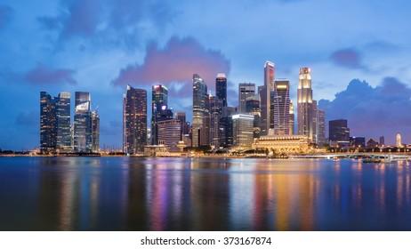 Colorful Singapore business district skyline after sun set at Marina Bay. Panoramic image.