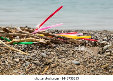 colorful single use plastic straws garbage washed up on the beach illustrating stop pollution