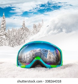 Colorful ski glasses on snow. Winter ski theme.
