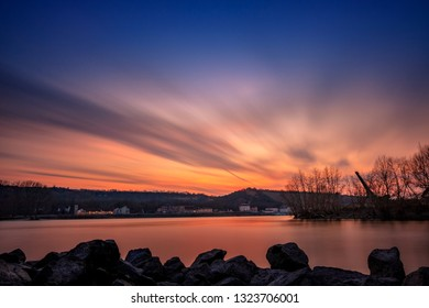 Colorful sky after the sunset, over the river Rhine. with sandy bay and in a long exposure. soft water in german winter