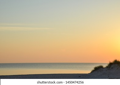 Colorful sky by a sandy beach by sunset at the swedish island Gotland