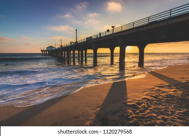 Colorful sky and clouds over Manhattan Beach Pier at sunset with long shadows cast on the beach, Manhattan Beach, California