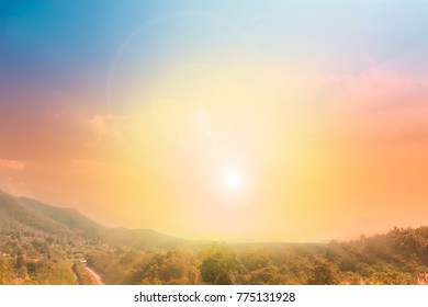 Colorful sky and clouds with sunlight, sunshine and lens flare on mountain and forest. Beautiful dramatic pastel nature sky landscape background on summer day concept