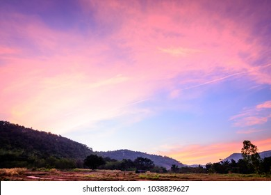 Colorful sky on the plain green, grass field with the background of trees and mountains at twilight before sunrise in Thailand. The beautiful sky has different colors: pink, purple, blue, and yellow.
