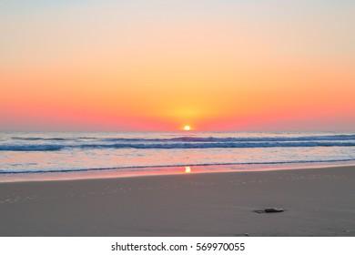 Colorful sky at sunset on the horizon at Lacanau Ocean sand beach near Bordeaux, France on the Atlantic coast