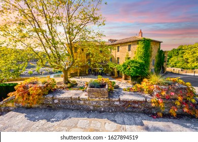 A colorful sky and sunset over a historic stucco mansion or country home along a river in the Provence area of Southern France at Autumn.