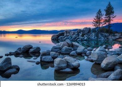 Colorful sky at sunset at Sand Harbor with calm water, beautiful rock formations, and mountains in the background, Lake Tahoe, Carson City, Nevada
