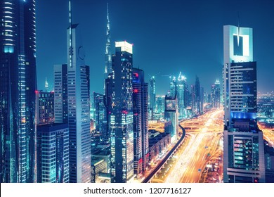 Colorful skyline of a big modern city with illuminated skyscrapers and highways. Aerial view over downtown Dubai, UAE. Travel and architectural background.