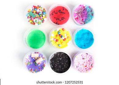 Colorful slimes inside plastic boxes. Kids gunk toy isolated over white background.