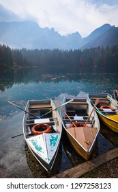 Colorful small boats in lake Laghi di Fusine near Tarvisio in Italyon a sunny morning with some clouds and fog