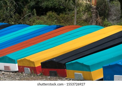 Colorful small fiberglass boat in a row on display out door