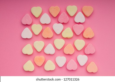 Colorful small hearts on the pink background